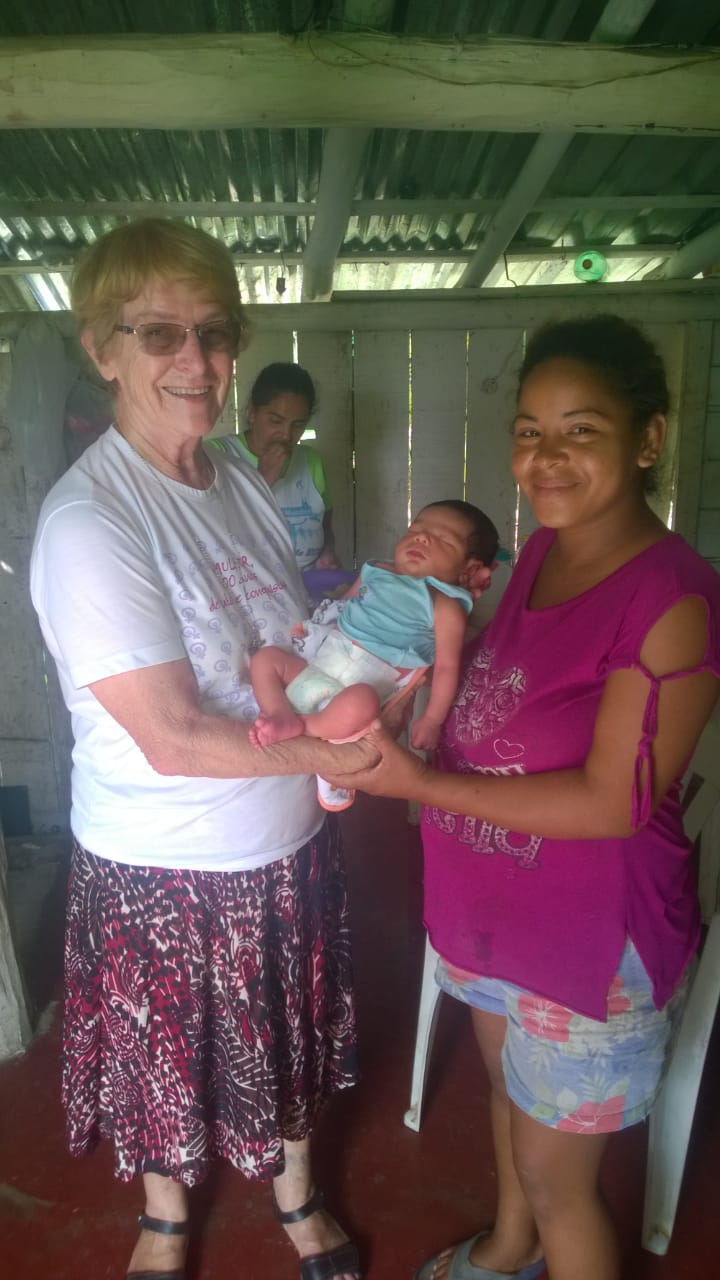 A Sister of St. Joseph of Chambery-Brazil province pictured with a Venezuelan mom and her four-day old baby.