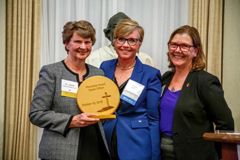 Karen Clifton receives the Founders Award from Sr. Janet Fleischhacker and Mary Novak. (Photo provided by Catholic Mobilizing Network)